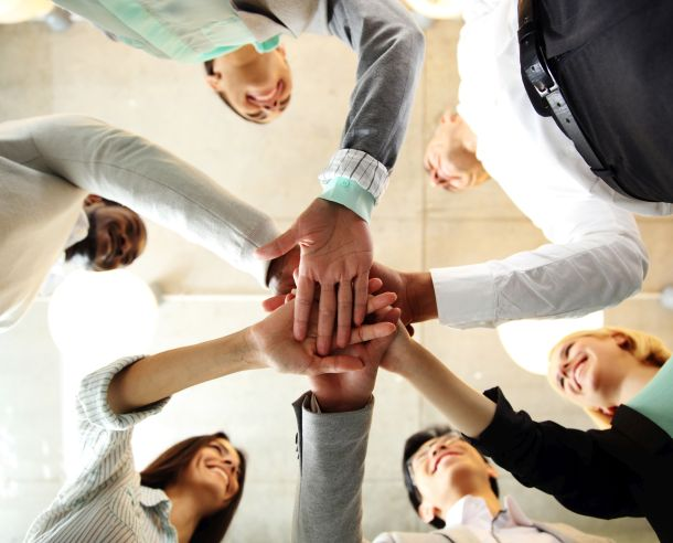 business people in an office with hands together - Highlighting ITI's commitment to teamwork