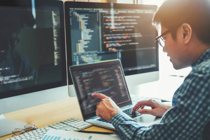 Computer programmer working on website development design and coding technology