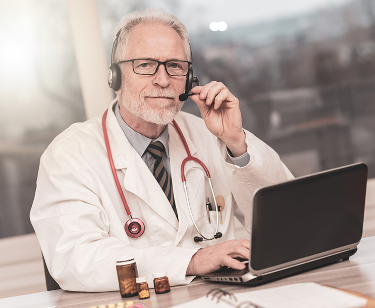 telehealth doctor using laptop with headset