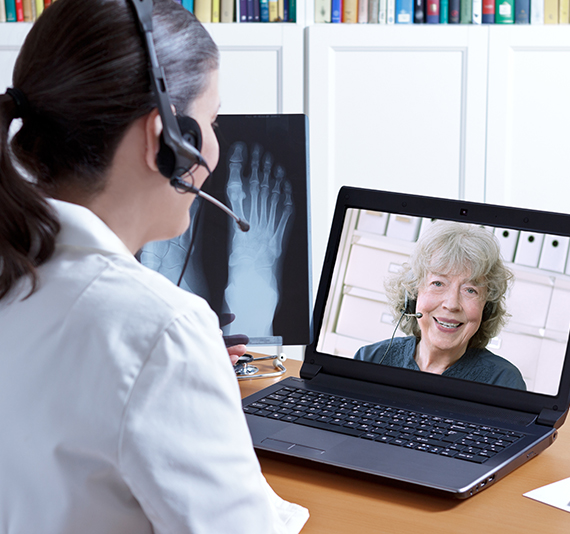 Female doctor using laptop for telehealth appointment with x-ray patient